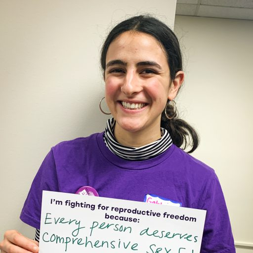 Gabbi Nazari holding paper that says every person deserves comprehensive Sex Ed